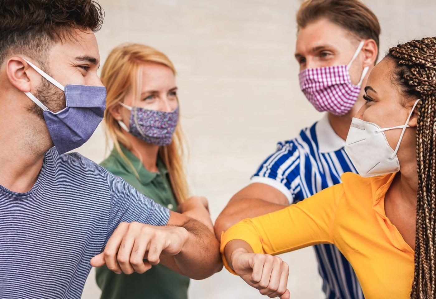 Grupo de amigos com máscara a cumprimentarem-se com o braço