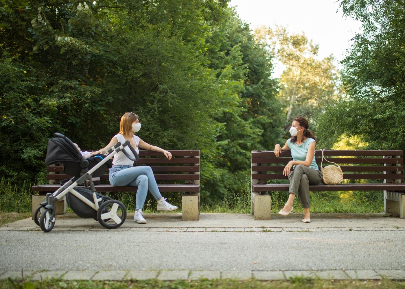 Duas mulheres a conversar no parque com máscara