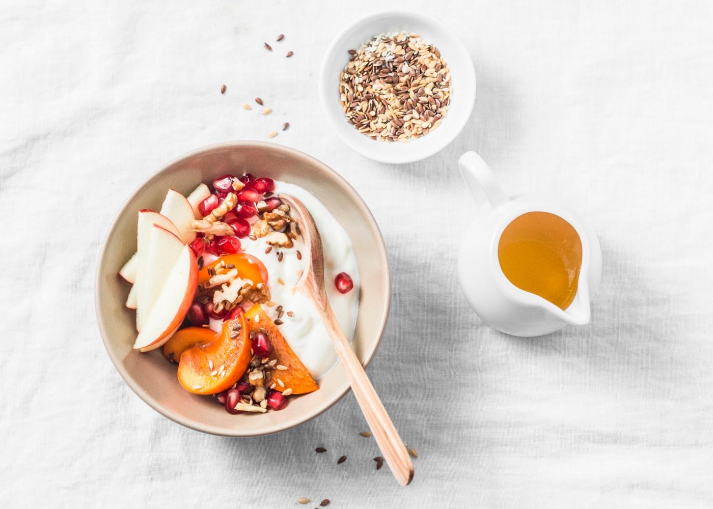 Taça com iogurte, maçã, dióspiro e romã