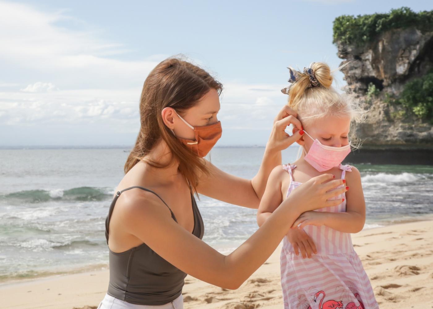 Mãe e filha na praia com máscara