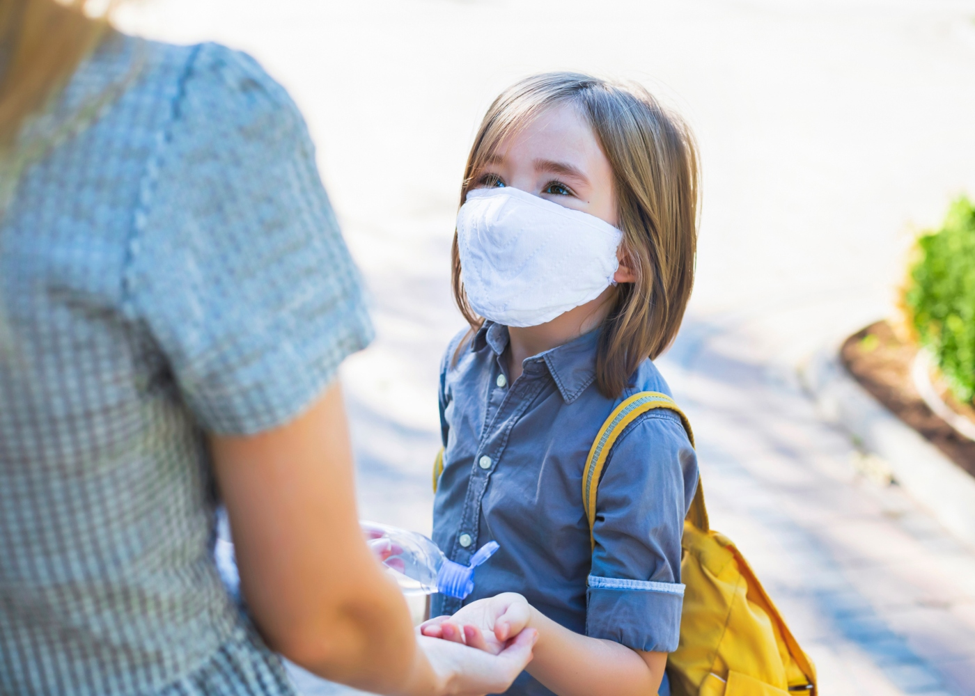 Mãe a conversar com filha sobre a importância de desinfetar mãos e usar máscara na escola