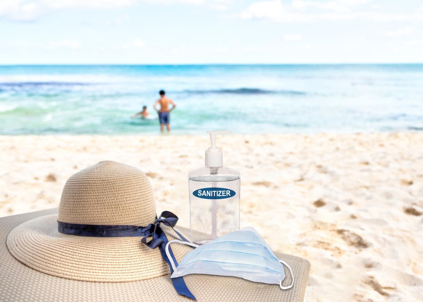 Máscara, chapéu e álcool-gel em cima de esteira na praia