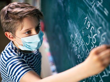 Menino numa aula a usar máscara
