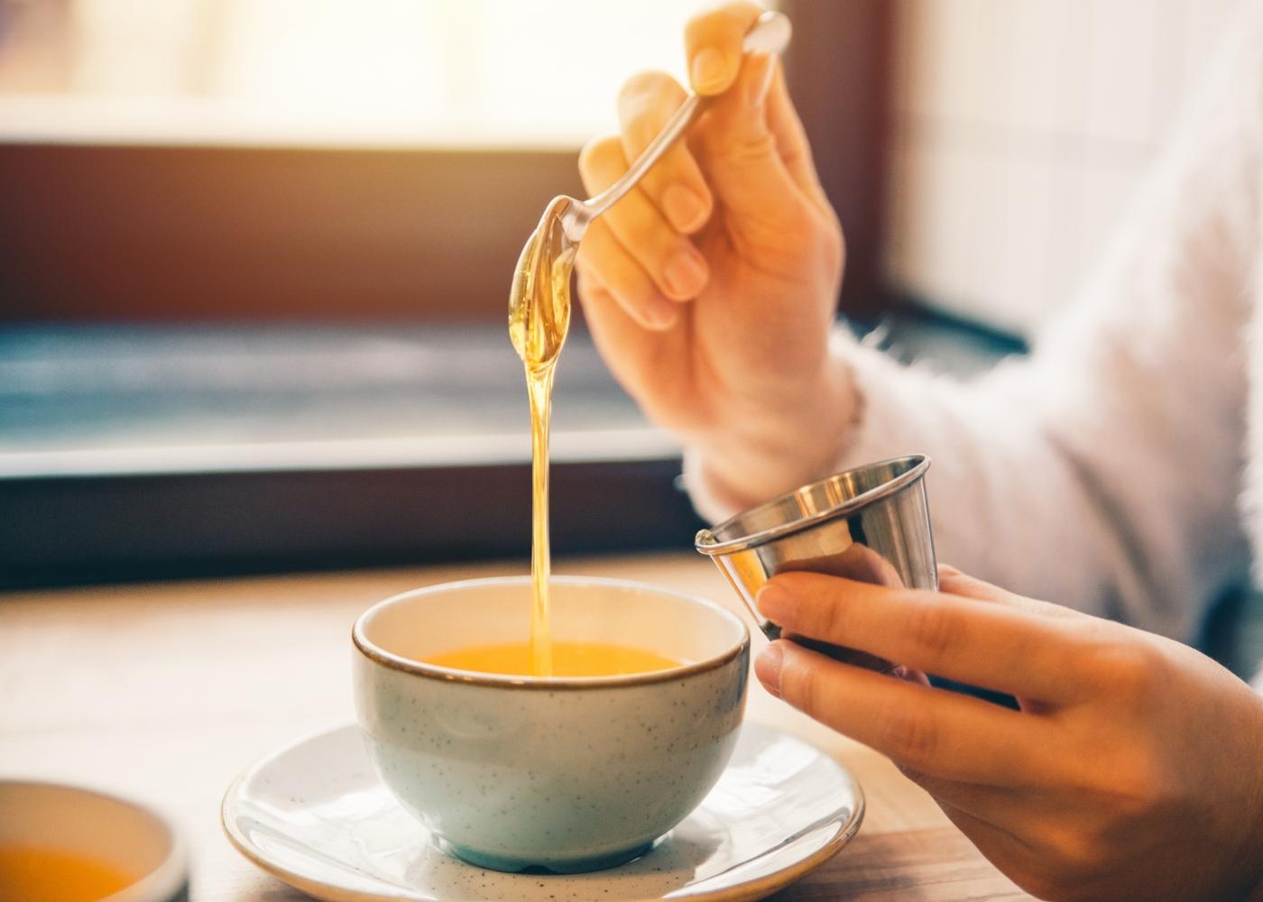 Mulher a adoçar o chá com mel