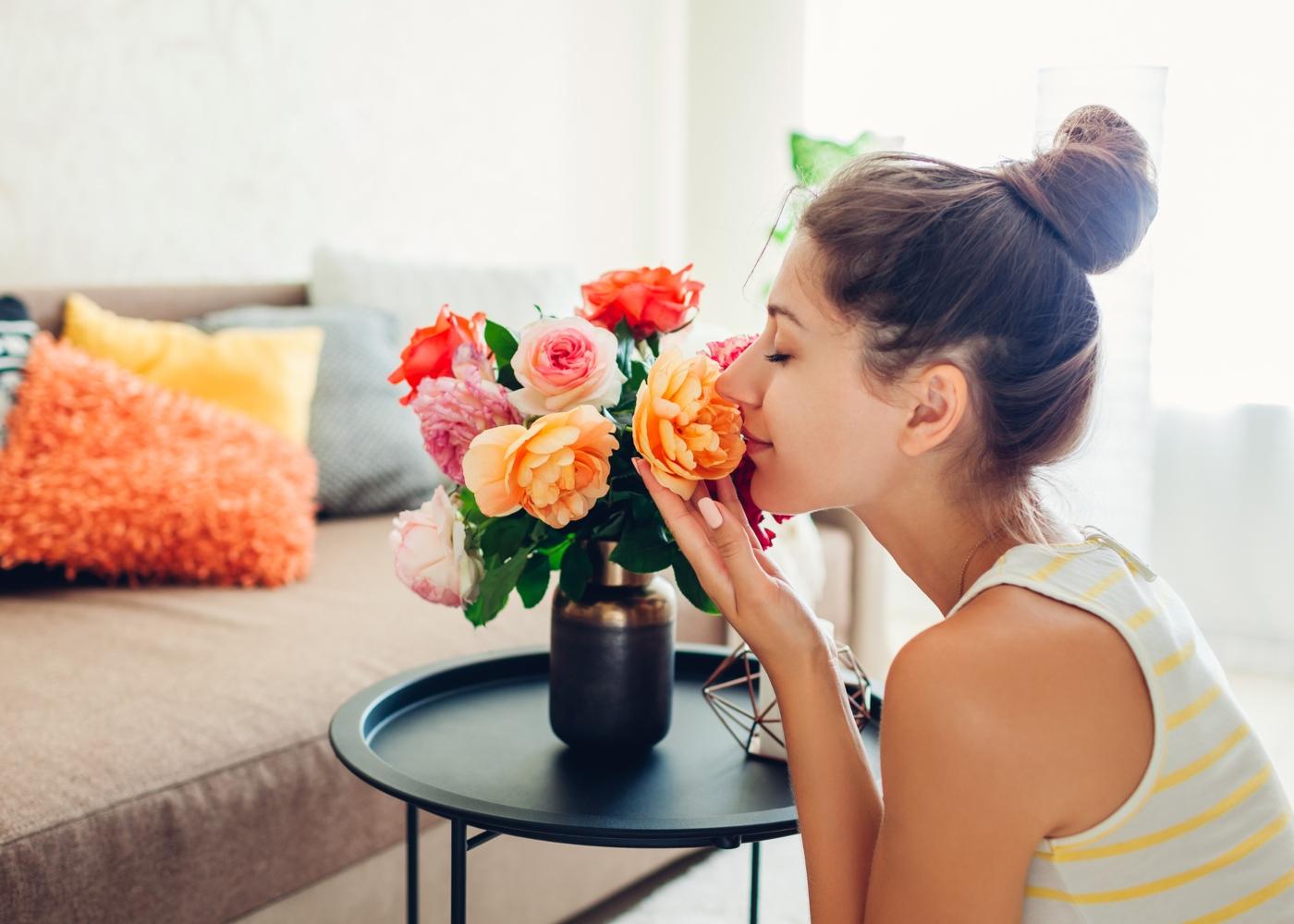 Mulher a cheirar flores