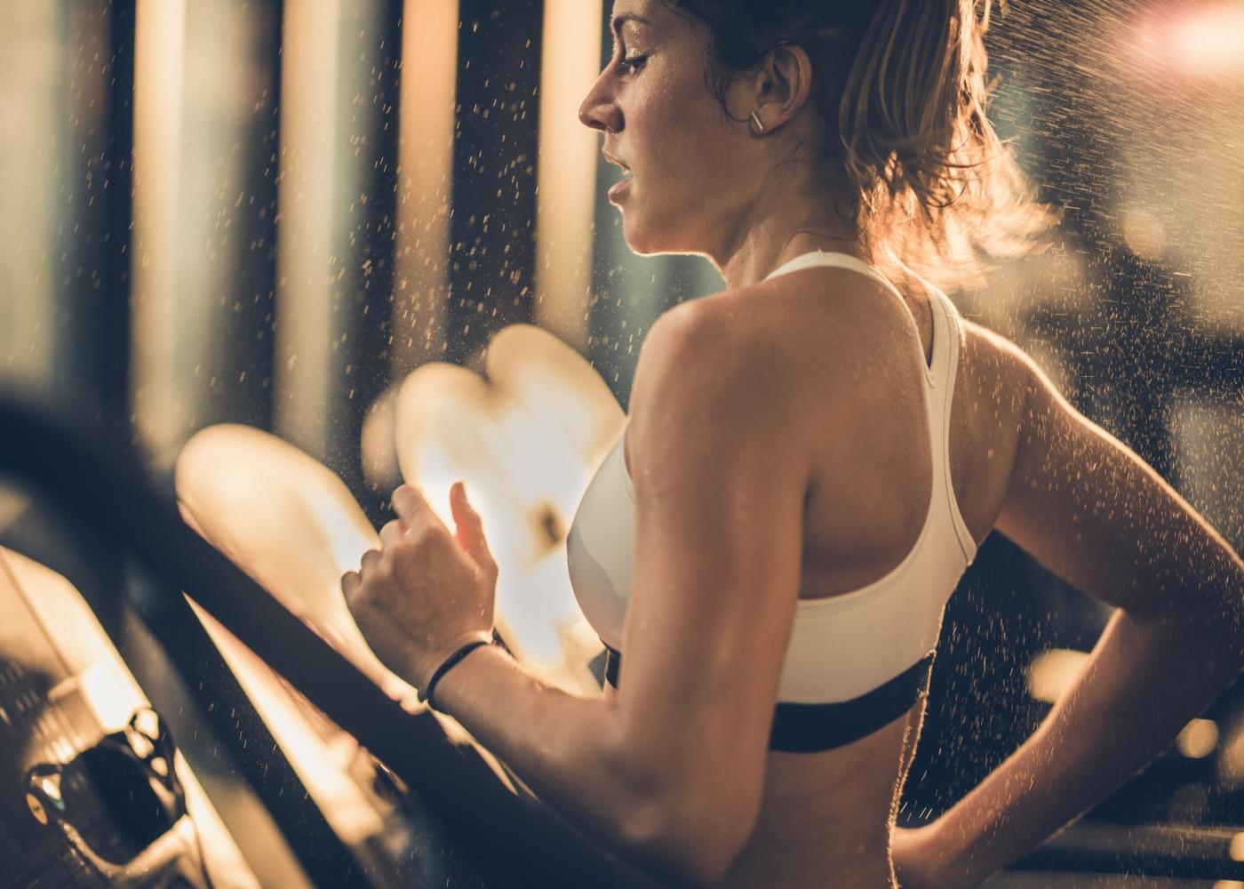 Mulher a correr em passadeira de ginásio