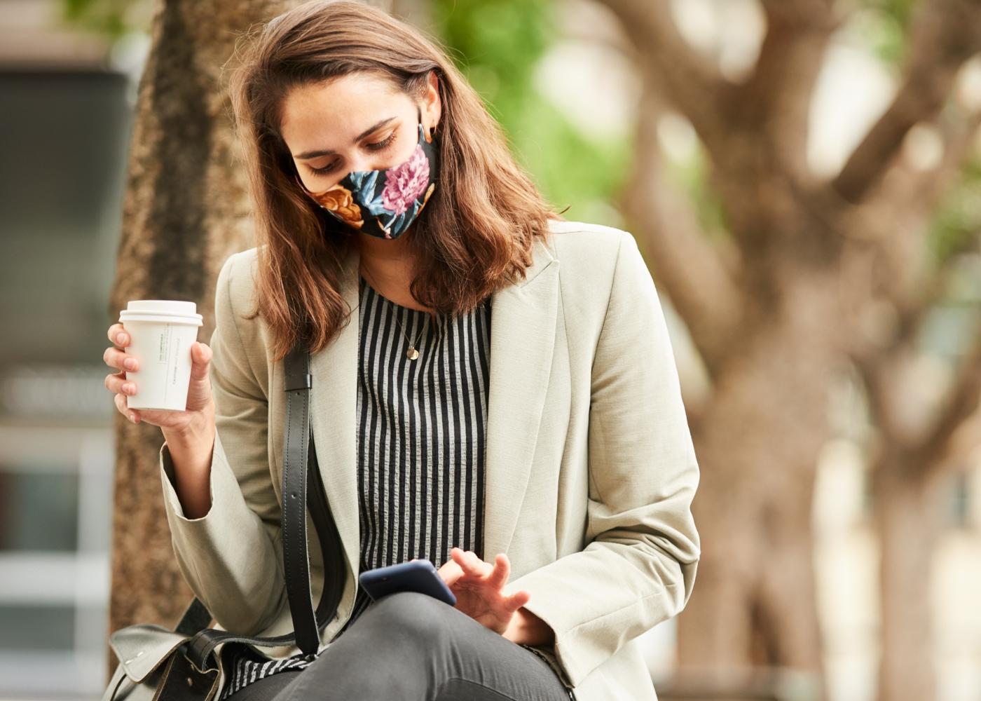 Mulher com máscara comunitária sentada no banco de um jardim