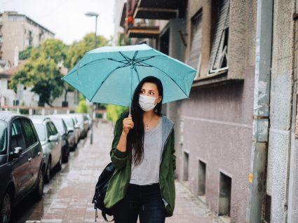 Mulher na rua com máscara num dia de chuva