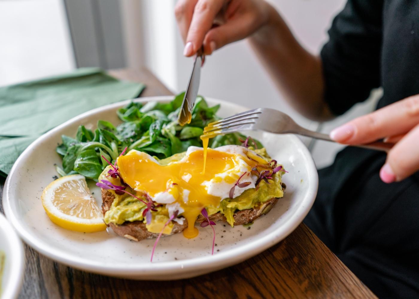Mulher a fazer refeição com ovo