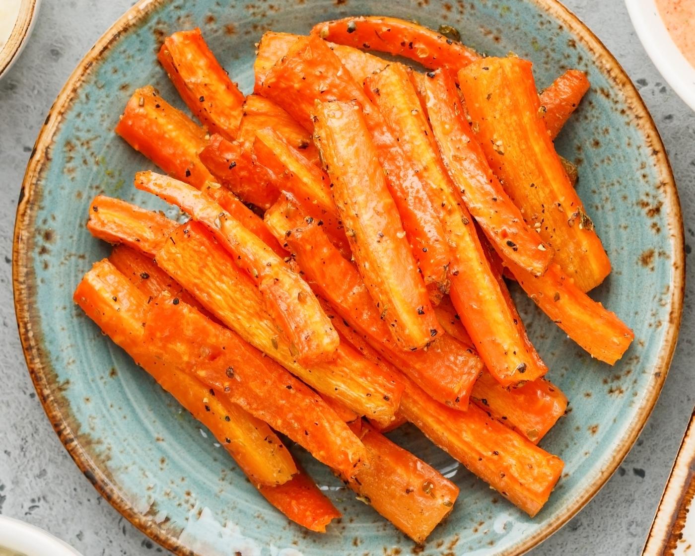 prato azul com palitos de cenoura no forno