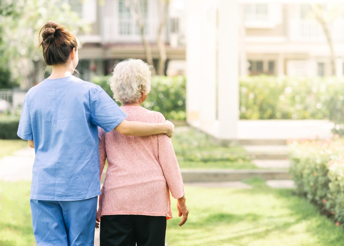 profissional de saúde a passear com idosa