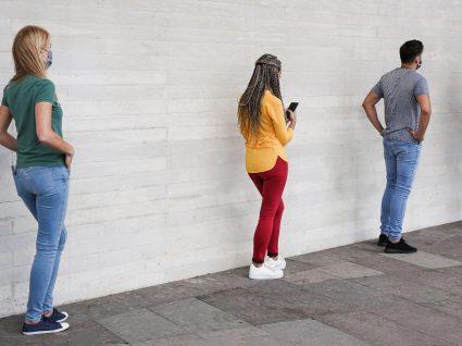 Mulher a utilizar a app Social Meter numa fila de entrada para loja