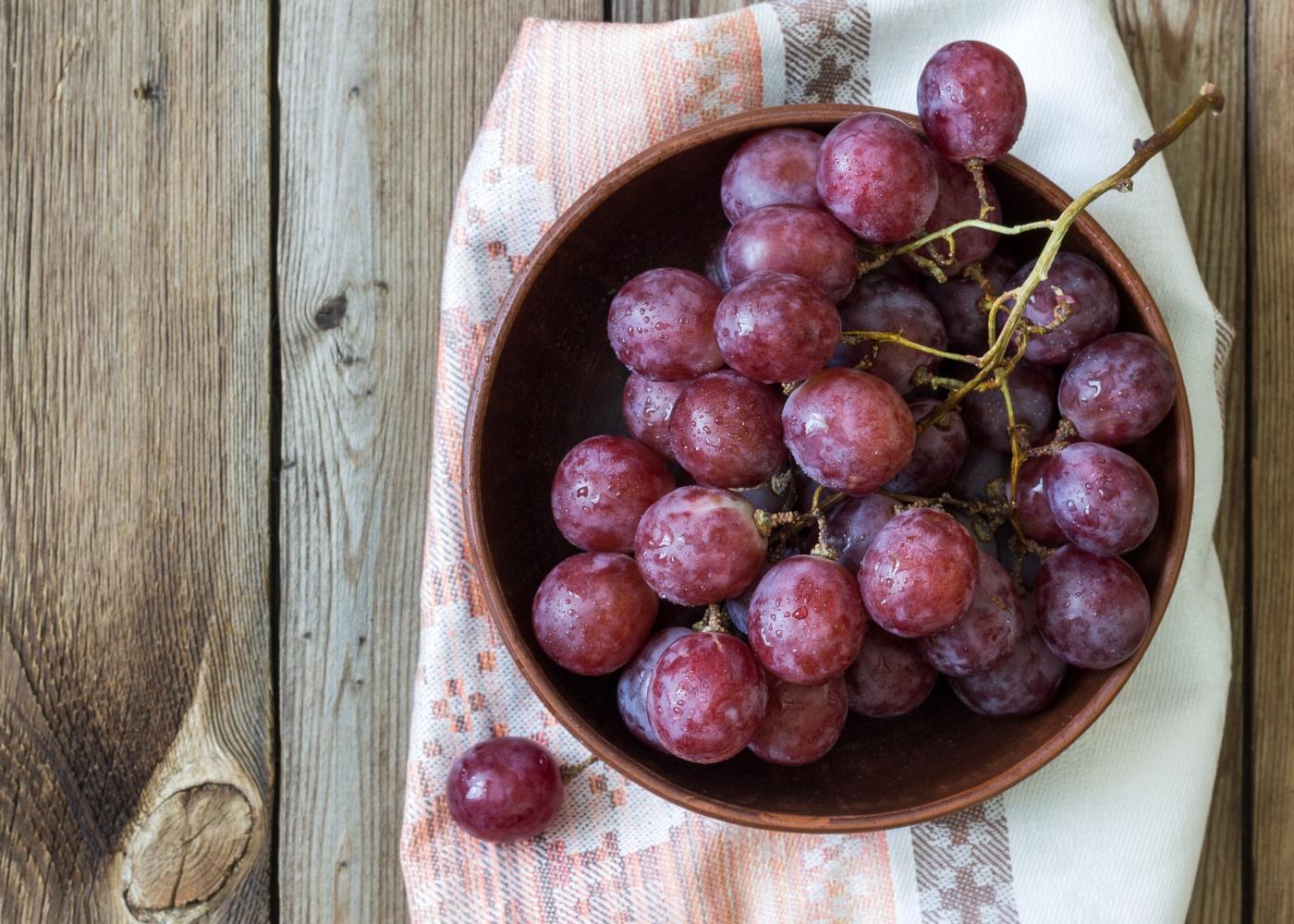 Taça com uvas em cima de mesa de madeira