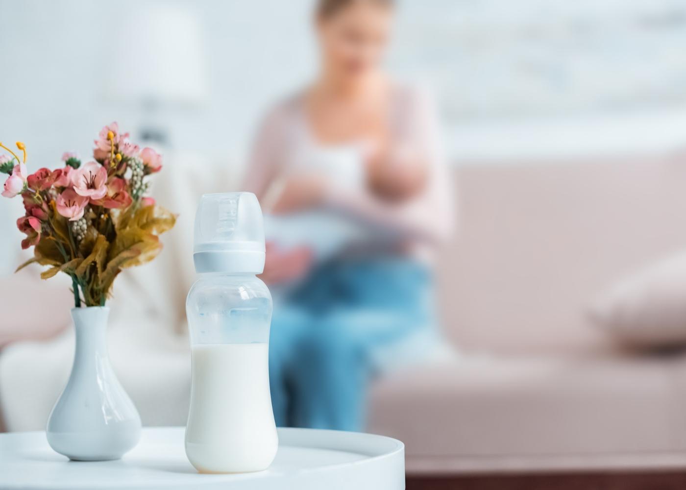 Biberão com leite em cima de mesa