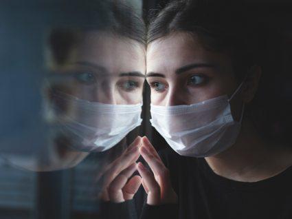 Cuidados de saúde mental: mulher de máscara a olhar pela janela