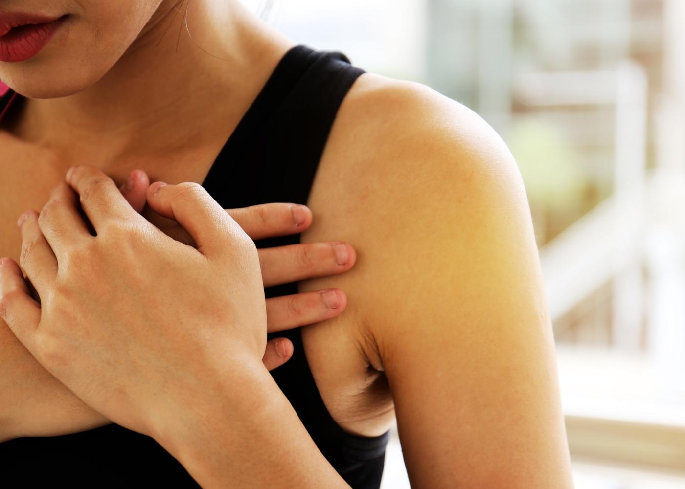 Mulher com dor no peito durante treino