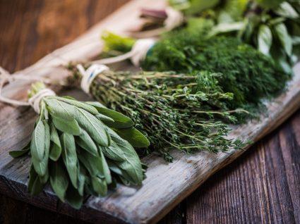 Ervas aromáticas em cima de tábua de cozinha