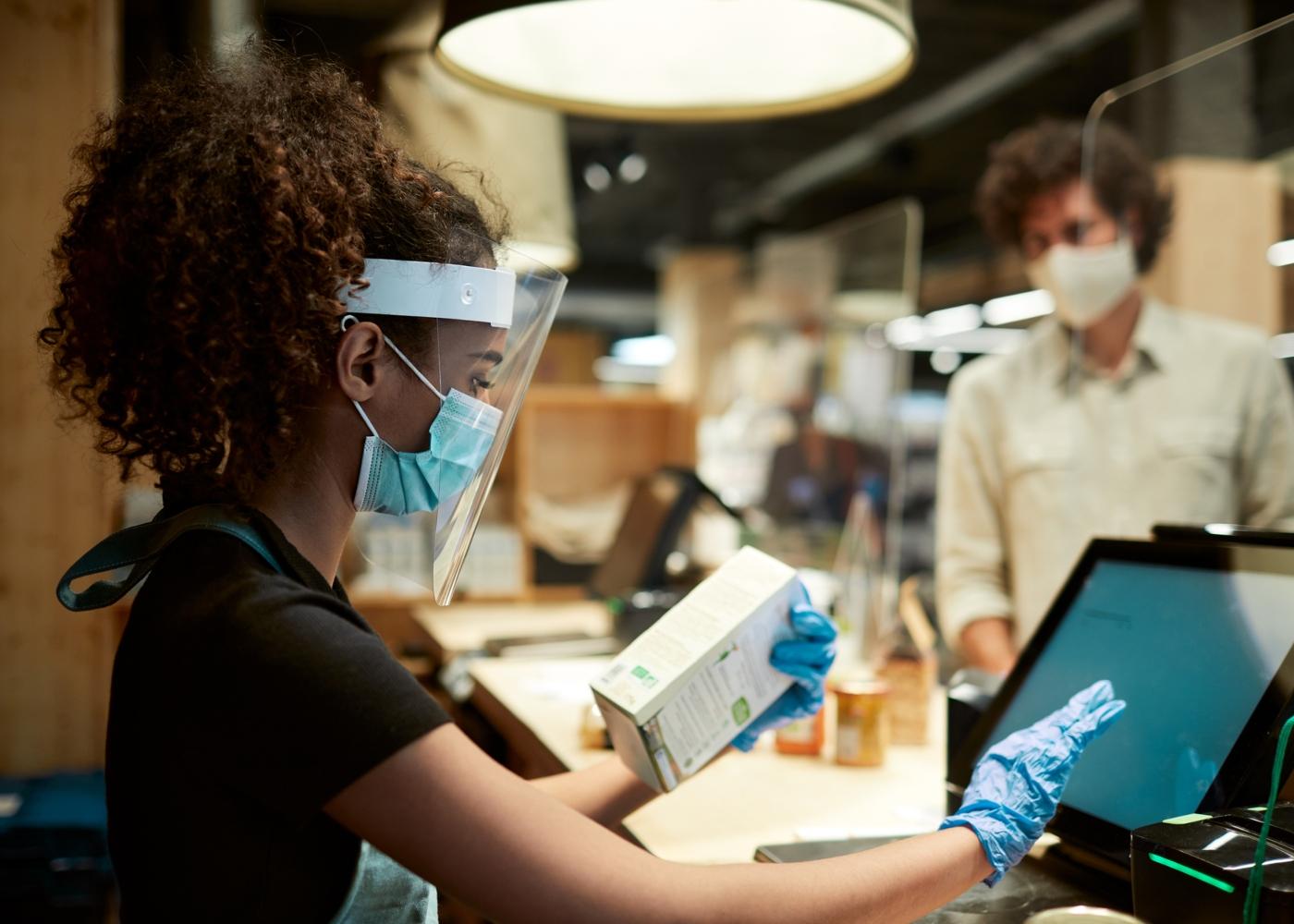 Funcionária de loja com viseira e máscara
