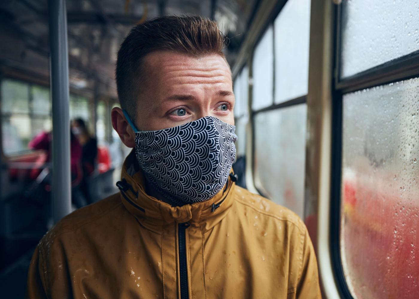 Homem com máscara comunitária no autocarro