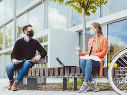 Casal de jovens a conversar com máscara