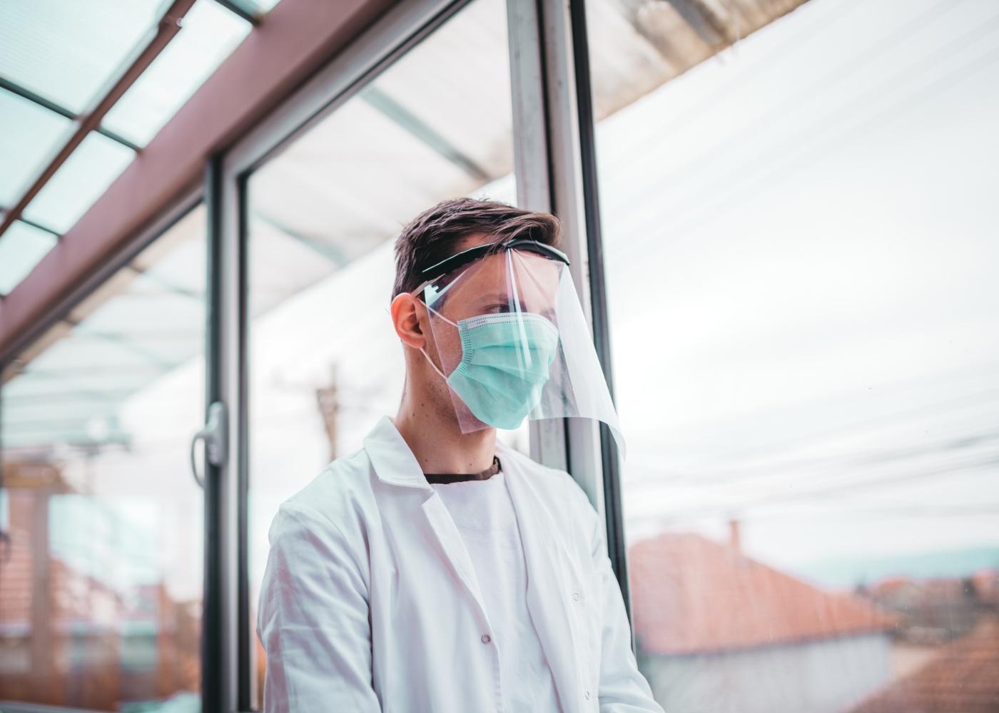 Médico com viseira e máscara