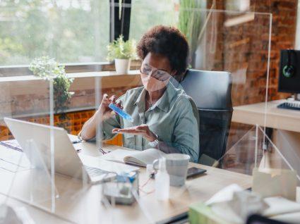 Mulher no local de trabalho a desinfetar as mãos