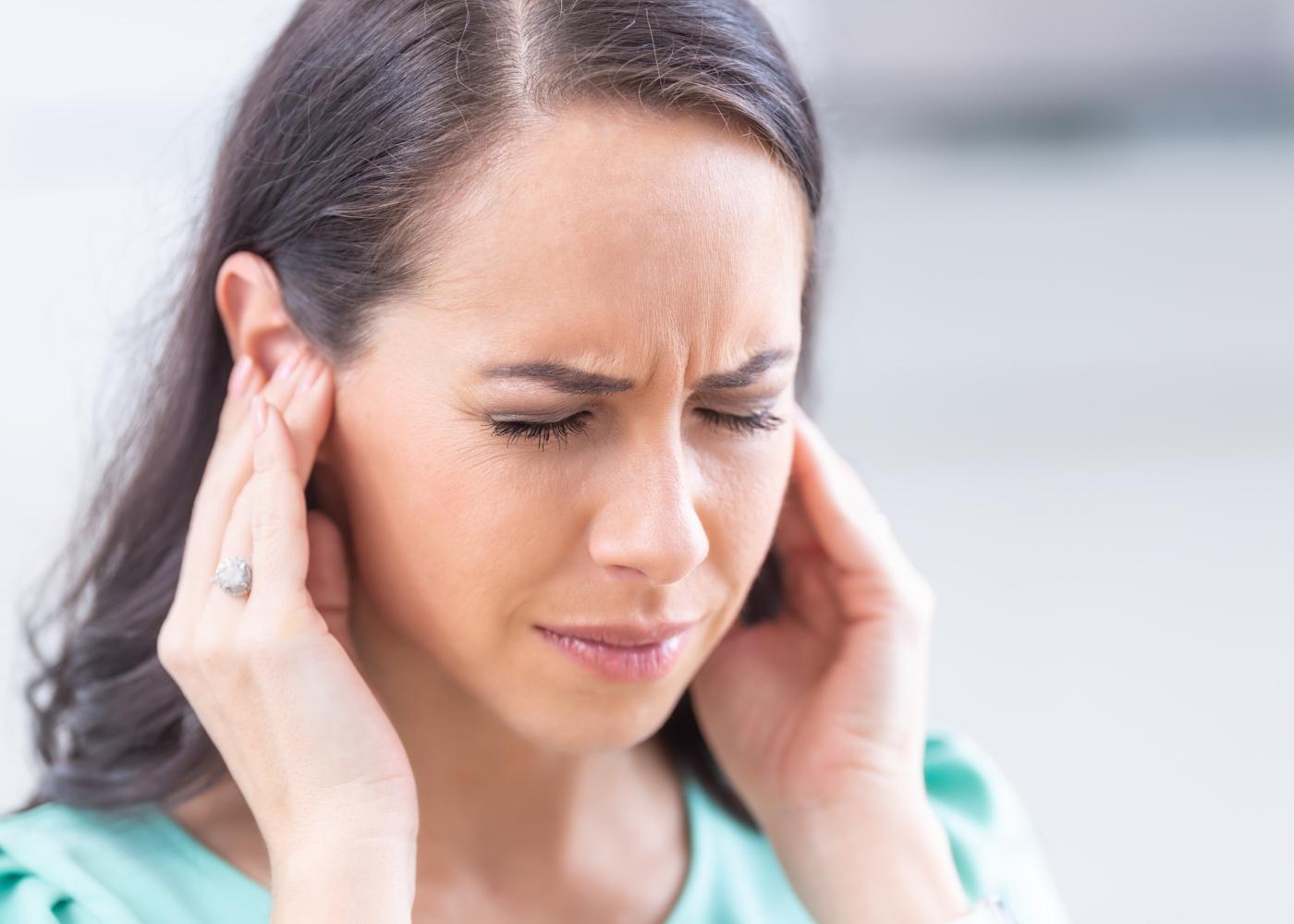Mulher com dores nos ouvidos