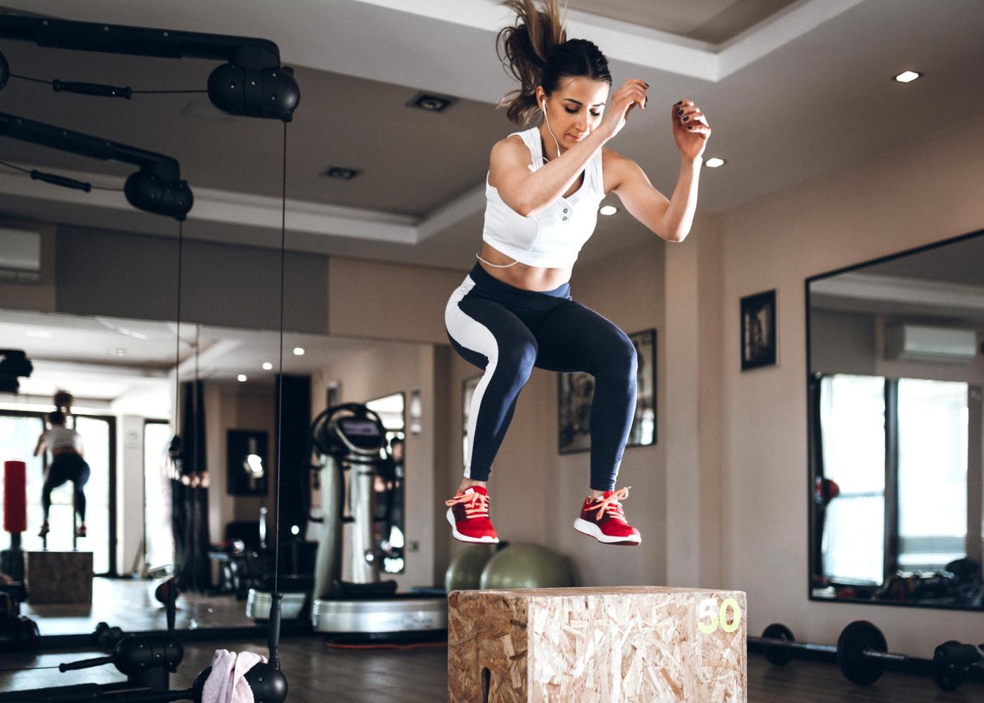 Mulher a saltar para uma Box no ginásio