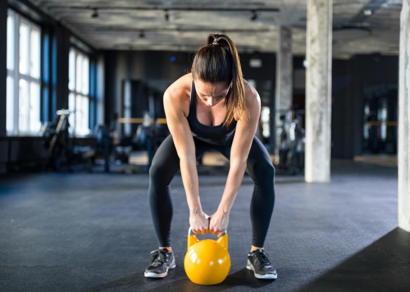 Mulher a fazer treino com kettlebell