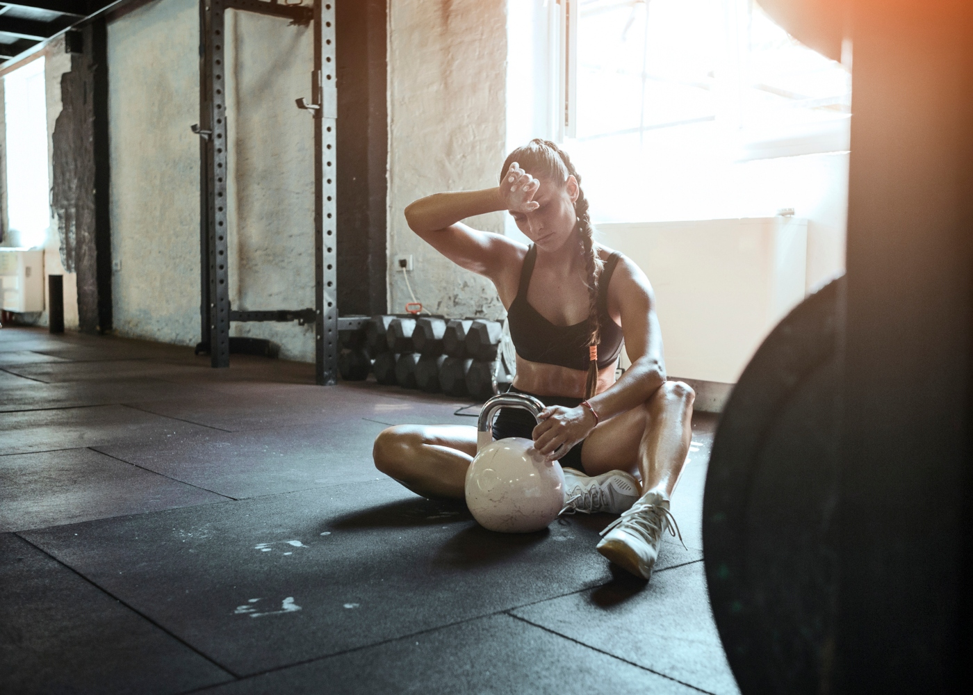 Mulher a descansar após realizar treino de força no ginásio