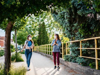 Duas mulheres com máscara a conversar na rua