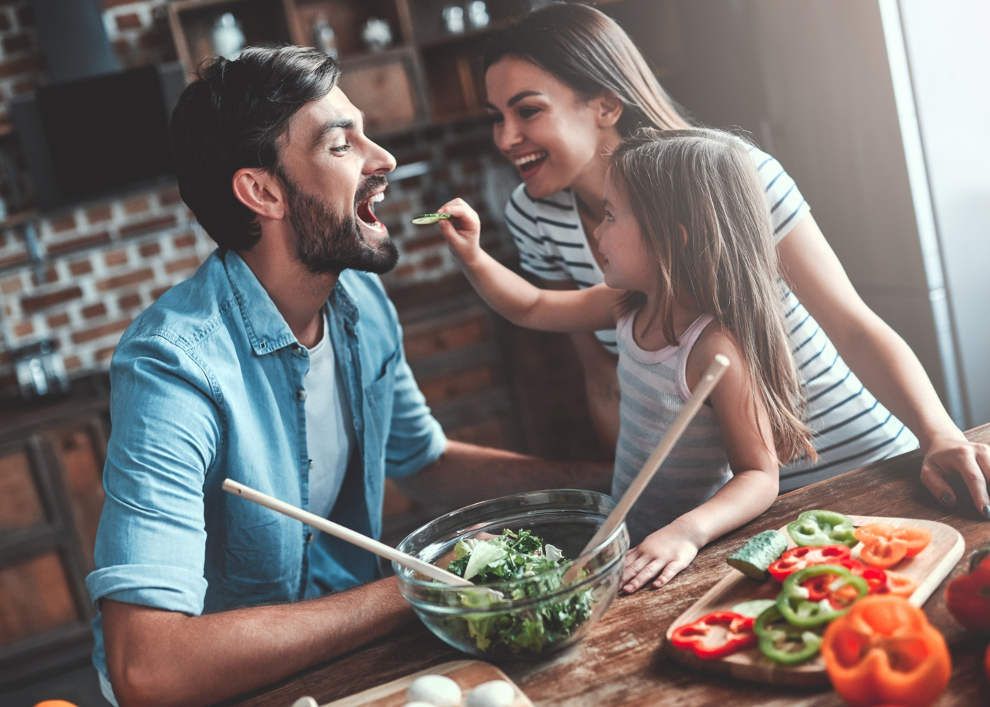 Pais e menina a preparar uma salada para o almoço