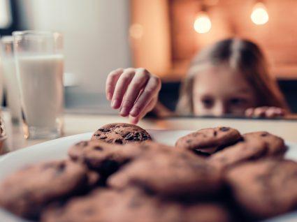 Menina a tirar bolachas de chocolate de tabuleiro