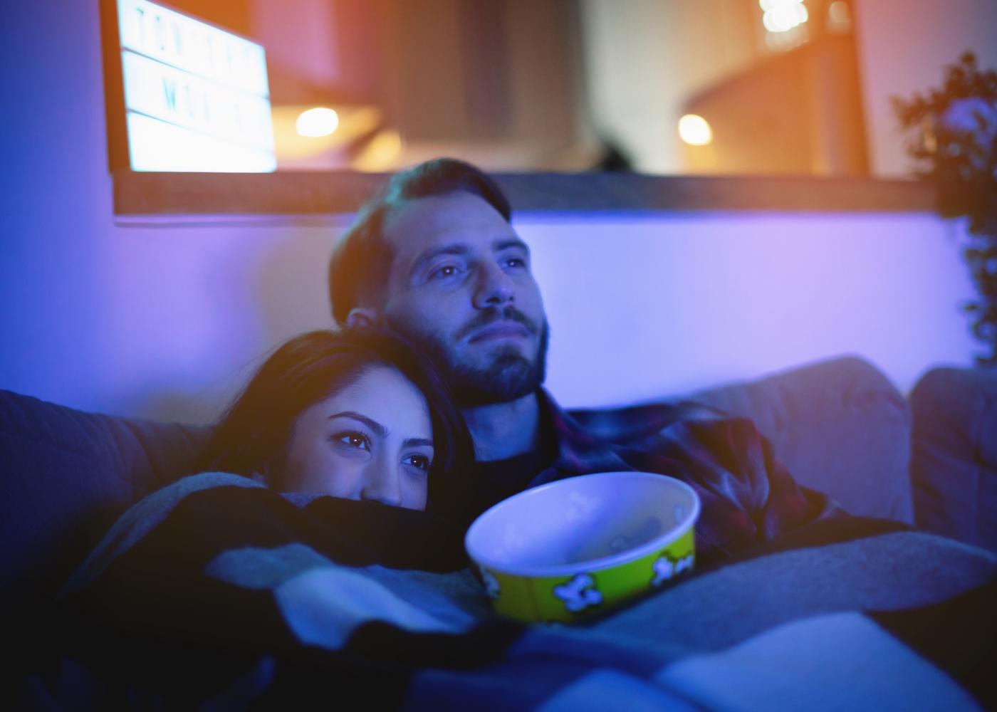 Casal em casa a ver um filme e a comer pipocas