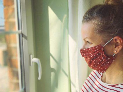 Mulher em casa a usar máscara reutilizável