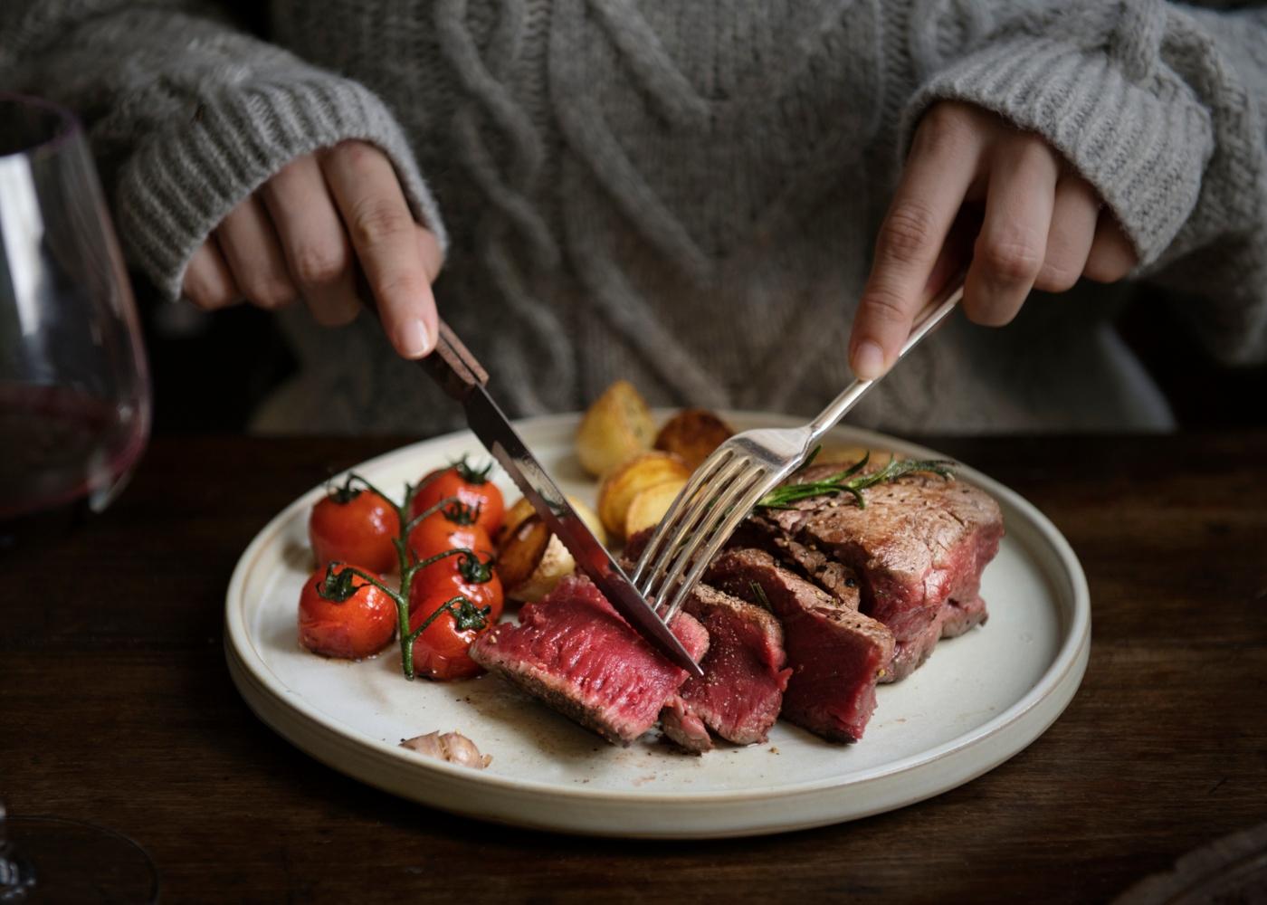 Mulher a comer bife suculento