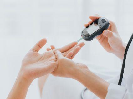 Médica a verificar níveis de açúcar no sangue de paciente