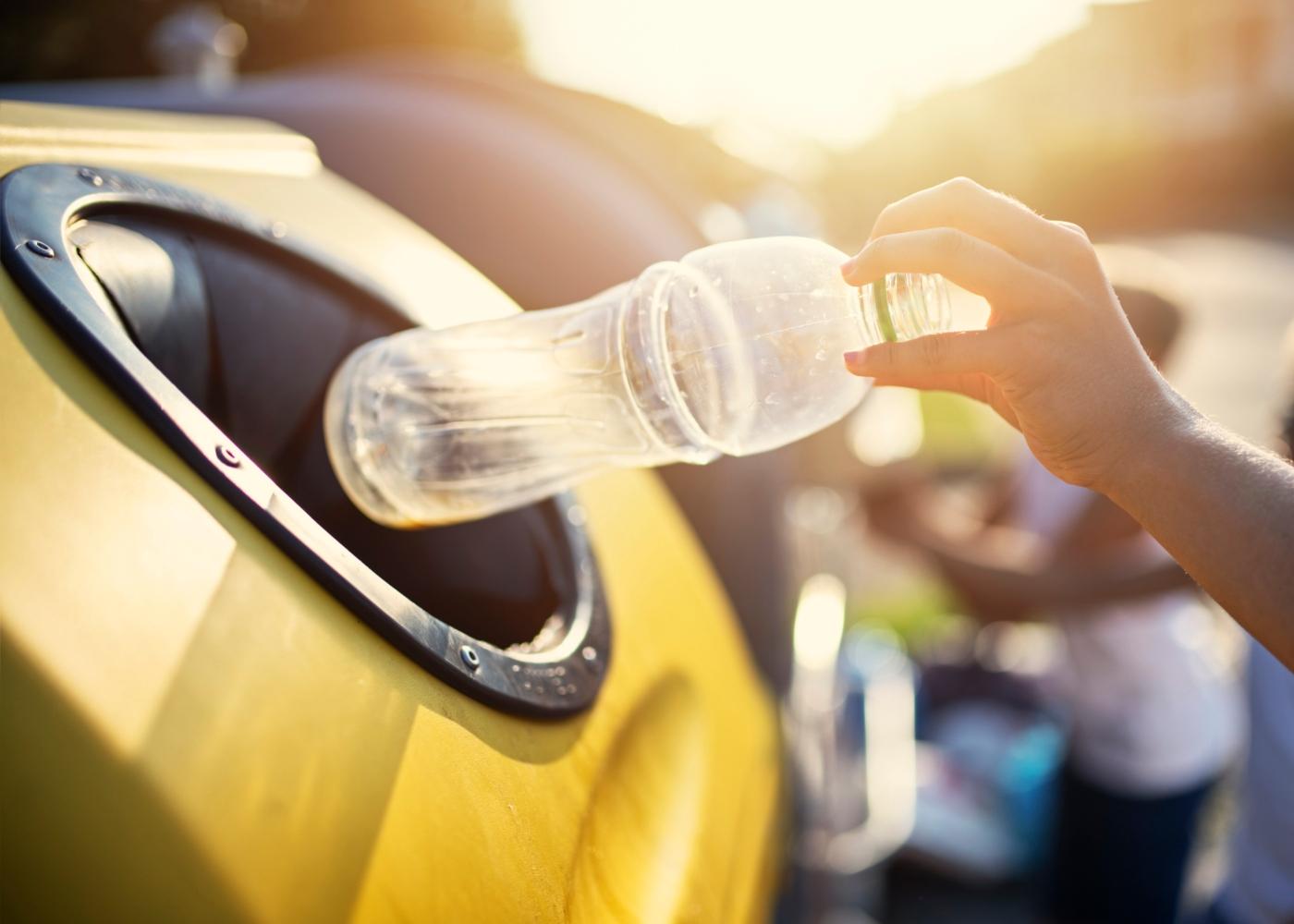 Mulher a colocar garrafa de plástico no ecoponto amarelo