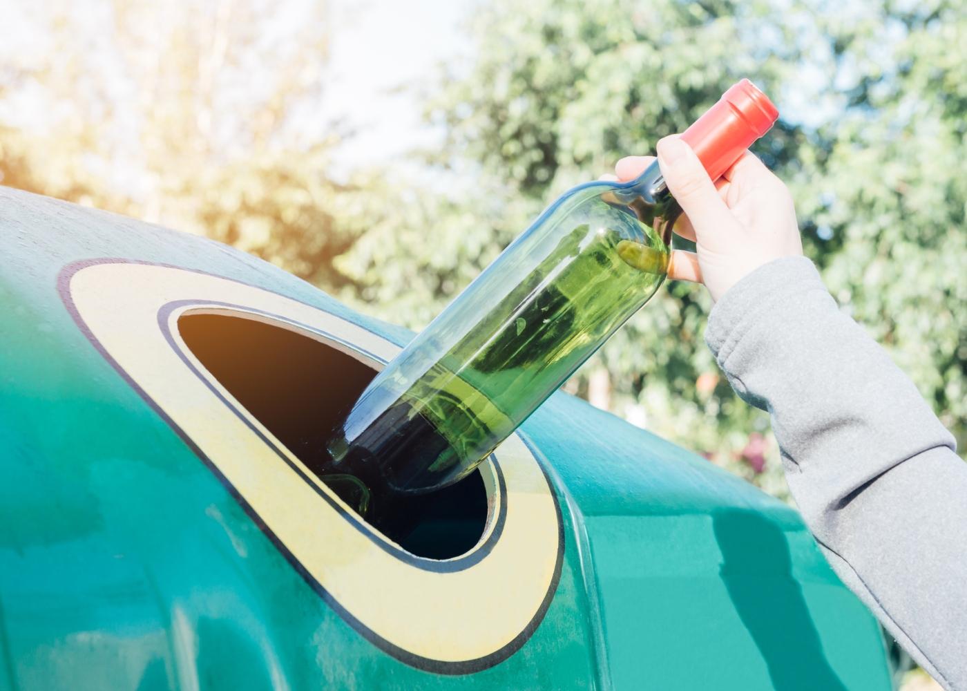 Mulher a colocar garrafa de vidro no ecoponto verde