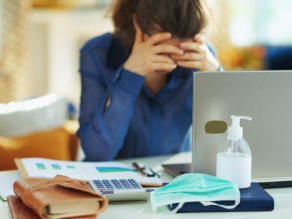 Mulher sentada numa secretária com ar cansado