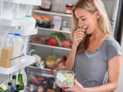 Mulher a comer fruta por ter fome antes do jantar
