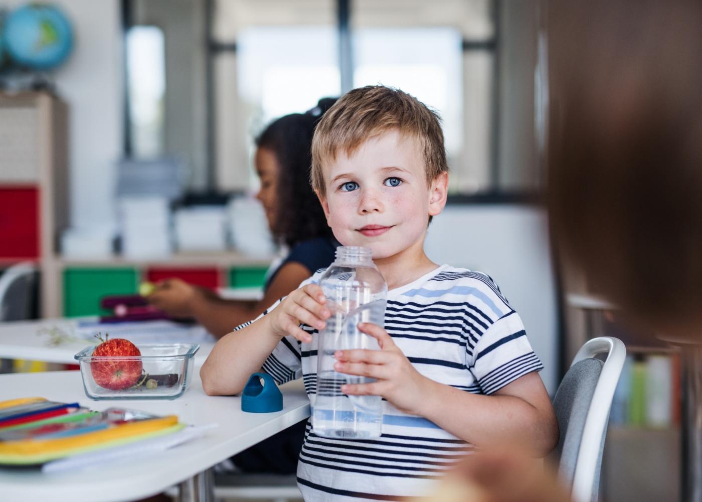Menino na escola a beber água