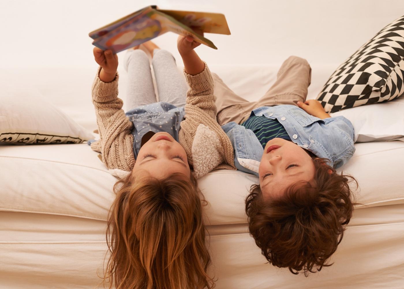 Irmãos a ler livro no sofá