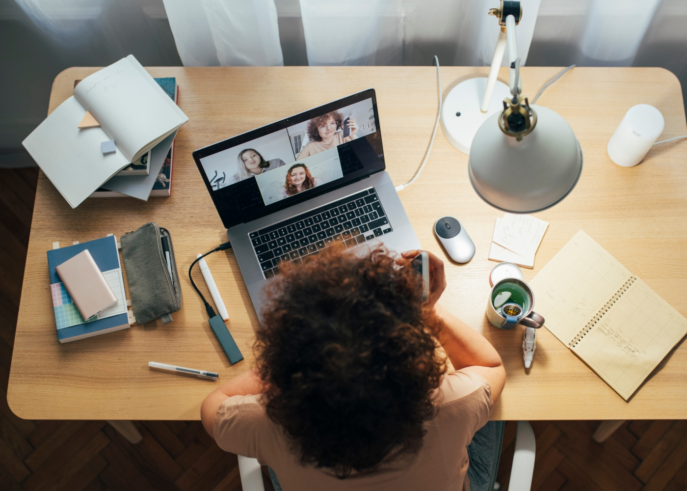 Mulher em casa a comunicar via Zoom com os colegas de trabalho