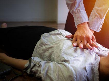 Homem a fazer manobras de Suporte Básico de Vida a uma mulher inconsciente