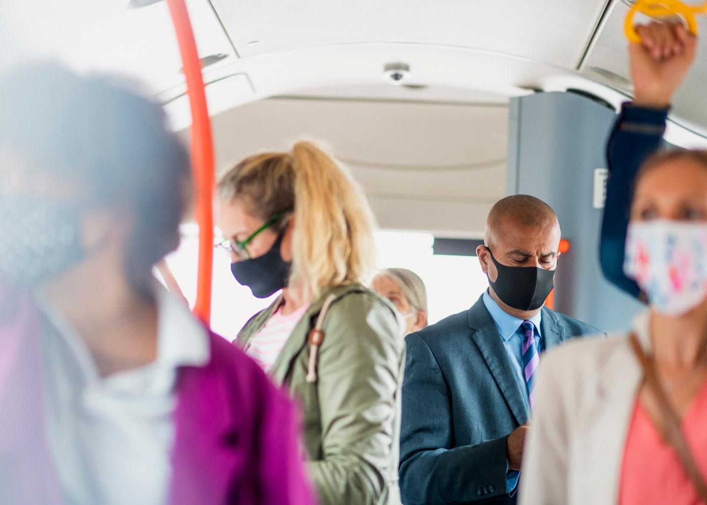 Pessoas com máscaras num autocarro