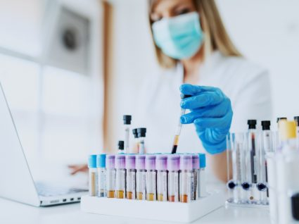 Técnica laboratorial a analisar amostras sanguíneas