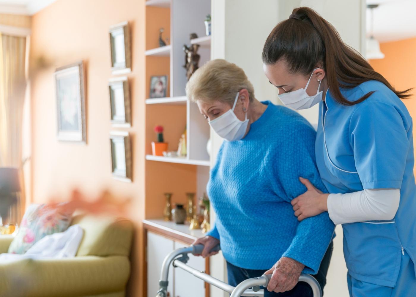 Mulher a prestar apoio a idosa com mobilidade reduzida