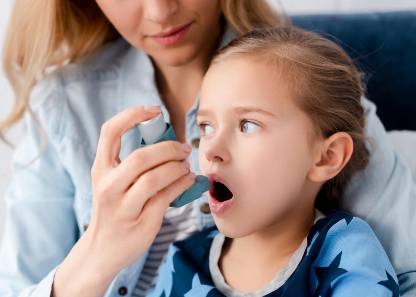 Criança com asma a utilizar o inalador