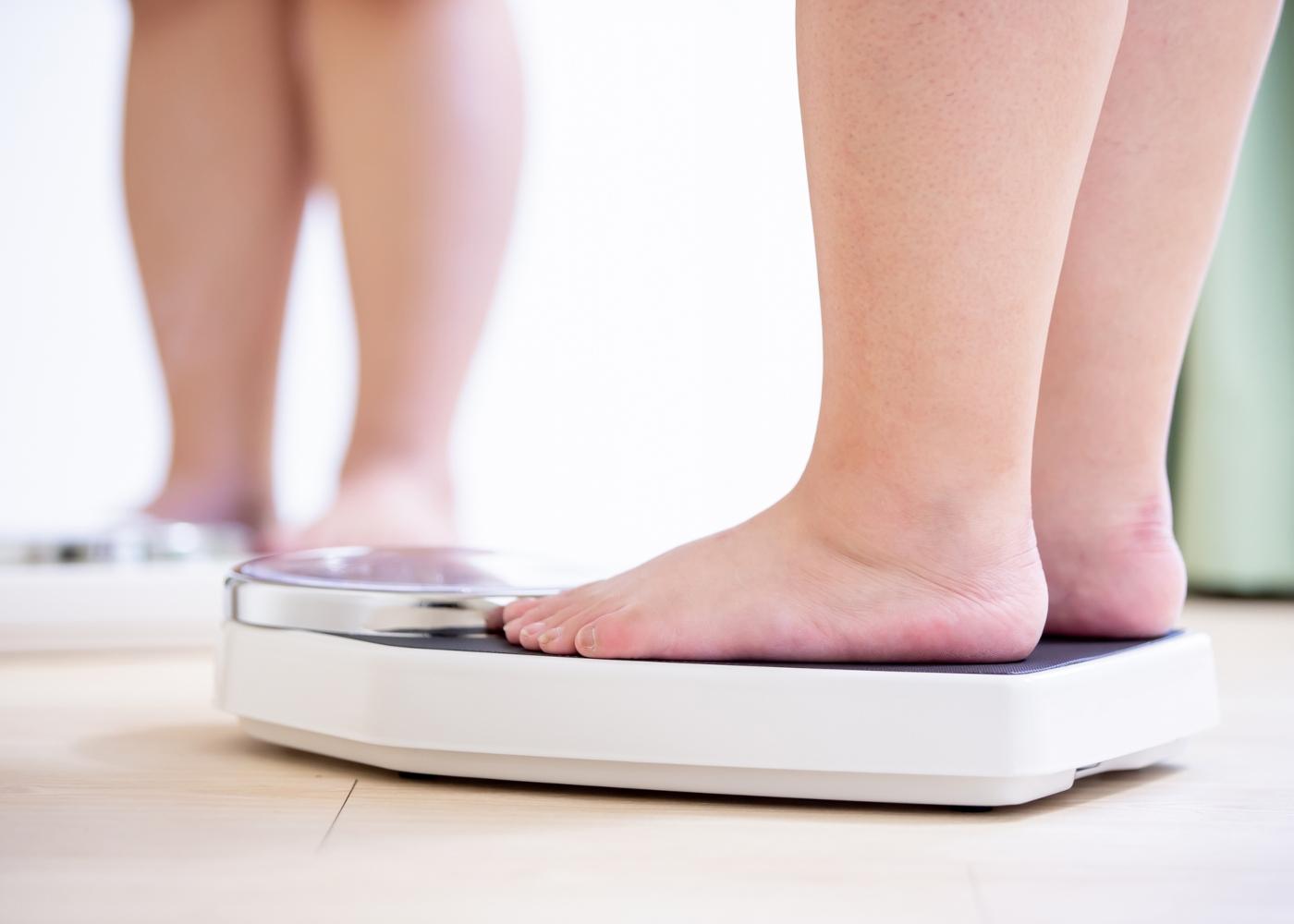 Mulher com excesso de peso a pesar-se numa balança